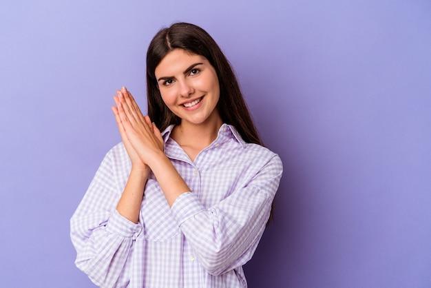 Młoda kaukaska kobieta na białym tle na fioletowym tle czuje się energiczna i wygodna, zaciera ręce pewnie.