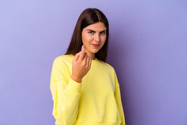 Młoda kaukaska kobieta na białym tle na fioletowym tle, wskazując palcem na ciebie, jakby zapraszając podejdź bliżej.