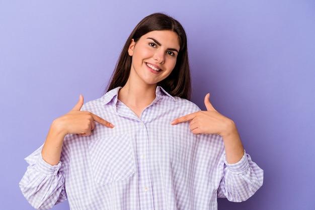Młoda kaukaska kobieta na białym tle na fioletowym tle zaskoczona, wskazując palcem, uśmiechając się szeroko.