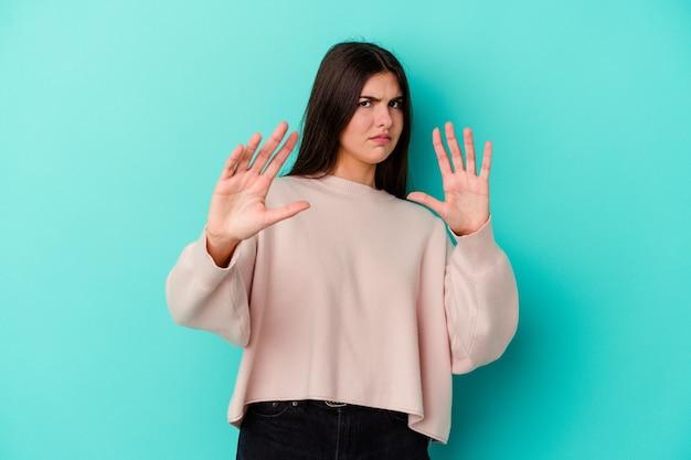 Młoda kaukaska kobieta na białym tle na niebieskiej ścianie odrzuca kogoś pokazującego gest obrzydzenia