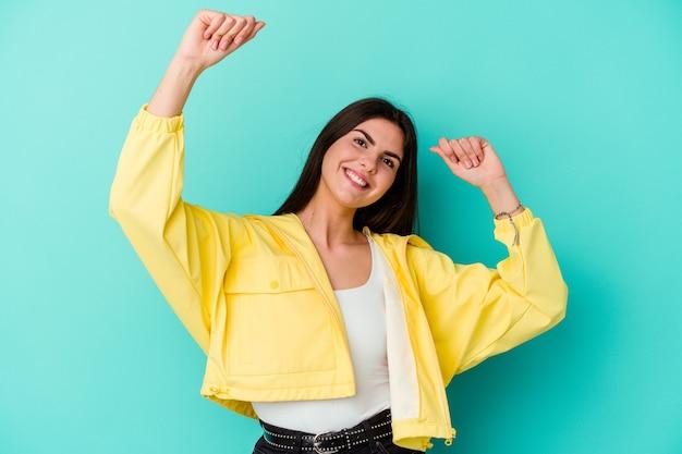Młoda kaukaska kobieta na białym tle na niebieskiej ścianie świętuje specjalny dzień, skacze i podnosi ręce z energią