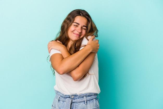 Młoda kaukaska kobieta na białym tle na niebieskim tle przytula się, uśmiechając się beztrosko i szczęśliwie.
