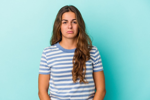 Młoda kaukaska kobieta na białym tle na niebieskim tle smutna, poważna twarz, czuje się nieszczęśliwa i niezadowolona.