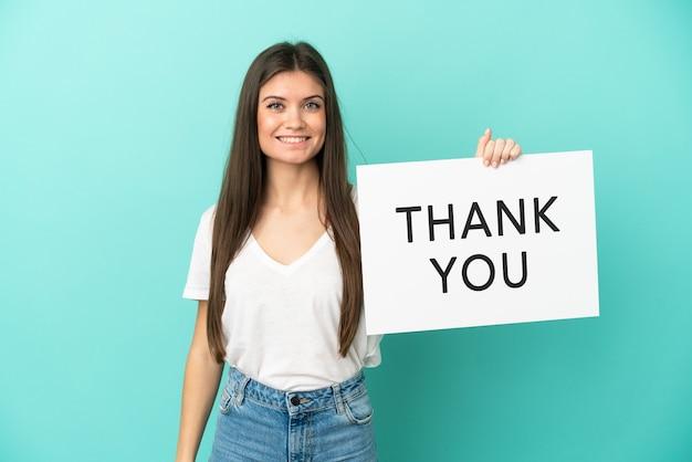 Młoda kaukaska kobieta na białym tle na niebieskim tle trzymająca afisz z tekstem dziękuję ze szczęśliwym wyrazem