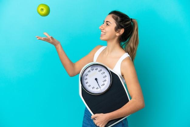 Młoda kaukaska kobieta na białym tle na niebieskim tle z wagą i jabłkiem
