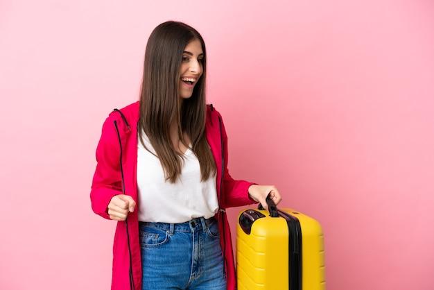 Młoda kaukaska kobieta na białym tle na różowym tle na wakacjach z walizką podróżną