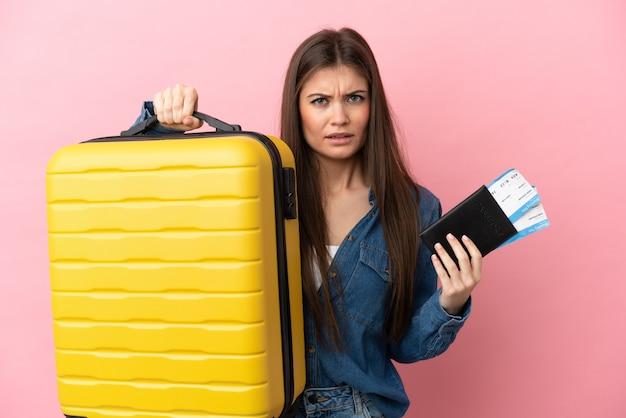 Młoda kaukaska kobieta na białym tle na różowym tle nieszczęśliwa na wakacjach z walizką i paszportem