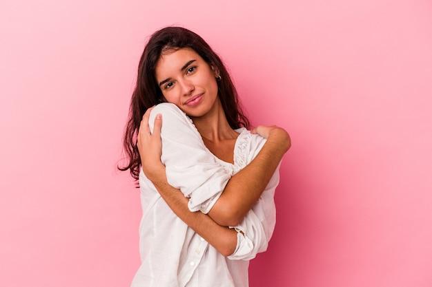 Młoda kaukaska kobieta na białym tle na różowym tle przytula się, uśmiechając beztrosko i szczęśliwie.