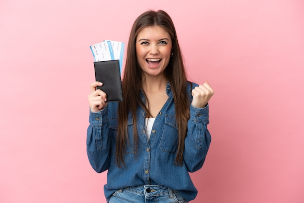 Młoda kaukaska kobieta na białym tle na różowym tle szczęśliwa na wakacjach z paszportem i biletami lotniczymi