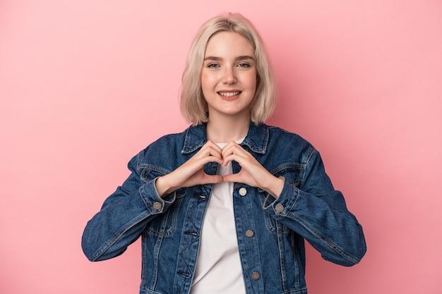 Młoda kaukaska kobieta na białym tle na różowym tle, uśmiechając się i pokazując kształt serca rękami.