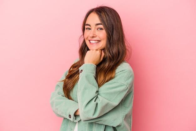 Młoda kaukaska kobieta na białym tle na różowym tle uśmiechnięta szczęśliwa i pewna siebie, dotykając ręką podbródka.