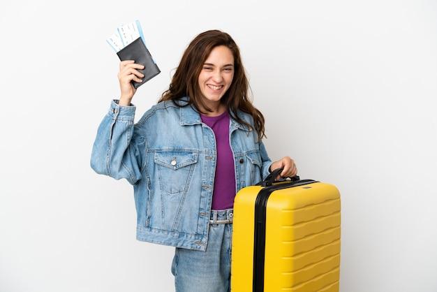 Młoda kaukaska kobieta na białym tle na wakacjach z walizką i paszportem