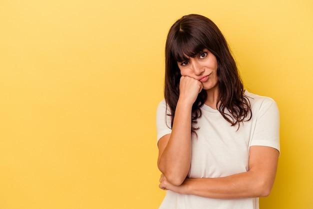 Młoda kaukaska kobieta na białym tle na żółtym tle, która czuje się smutna i zamyślona, patrząc na miejsce.