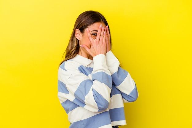 Młoda kaukaska kobieta na białym tle na żółtym tle mruga w aparat przez palce, zawstydzona zakrywająca twarz.