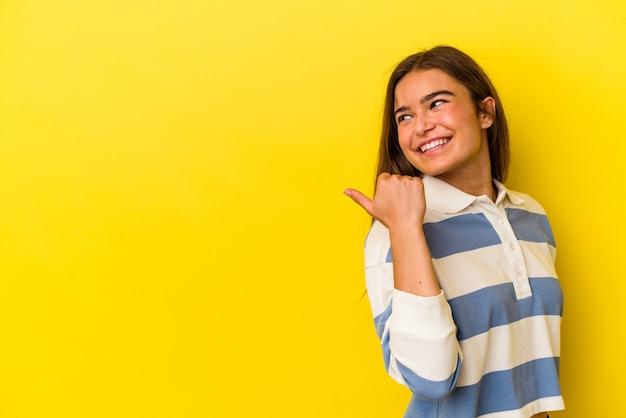 Młoda kaukaska kobieta na białym tle na żółtym tle wskazuje palcem kciuka, śmiejąc się i beztrosko.