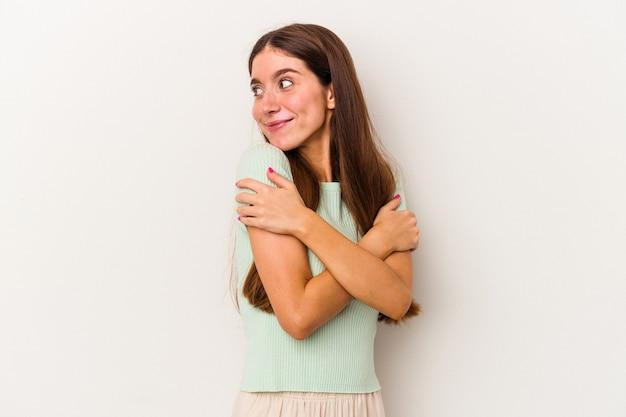 Młoda kaukaska kobieta na białym tle przytula się, uśmiechając się beztrosko i szczęśliwie.
