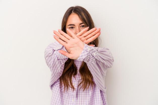Młoda kaukaska kobieta na białym tle robi gest odmowy
