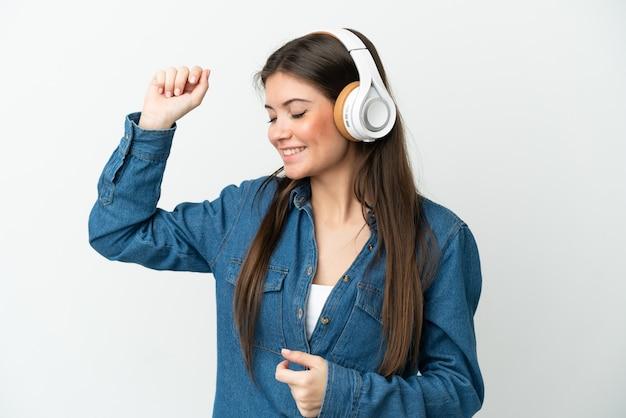 Młoda kaukaska kobieta na białym tle słucha muzyki i tańca