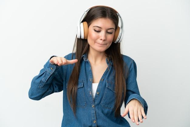 Młoda kaukaska kobieta na białym tle słuchając muzyki i tańcząc