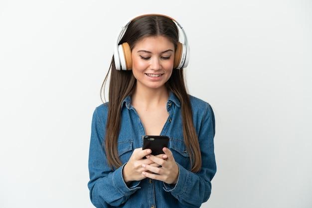 Młoda kaukaska kobieta na białym tle słuchająca muzyki i patrząca na telefon komórkowy