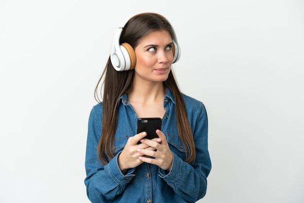 Młoda kaukaska kobieta na białym tle słuchająca muzyki za pomocą telefonu komórkowego i myślenia