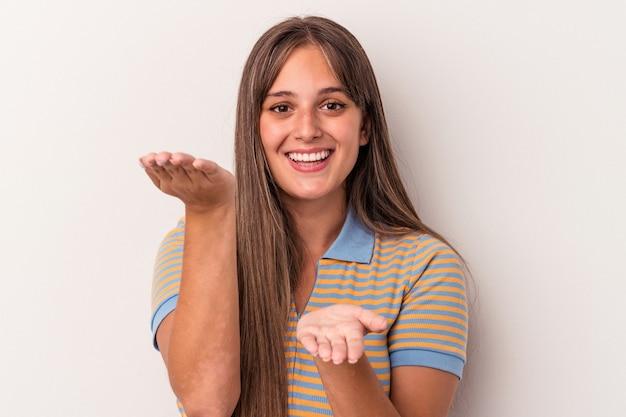 Młoda kaukaska kobieta na białym tle sprawia, że skala z rękami, czuje się szczęśliwa i pewna siebie.