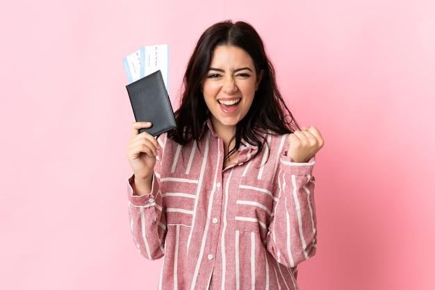 Młoda kaukaska kobieta na białym tle szczęśliwa na wakacjach z paszportem i biletami lotniczymi