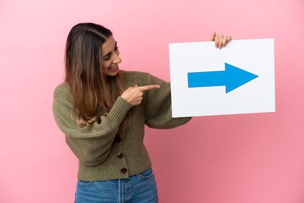 Młoda kaukaska kobieta na białym tle trzyma plakat z symbolem strzałki i wskazuje go