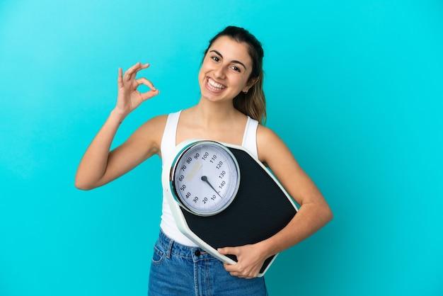 Młoda kaukaska kobieta na białym tle trzyma wagę i robi znak ok