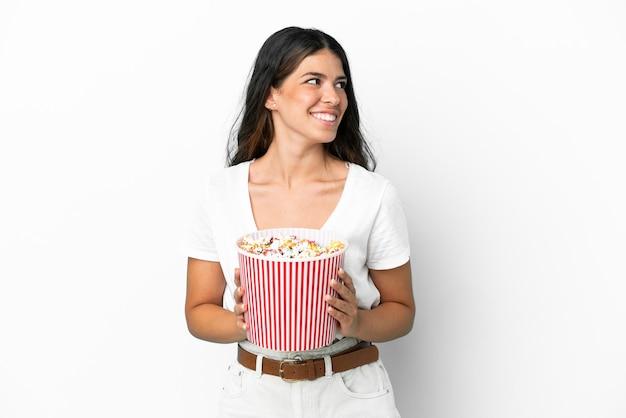 Młoda kaukaska kobieta na białym tle trzymająca duże wiadro popcornów