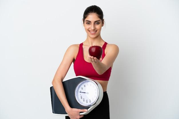 Młoda kaukaska kobieta na białym tle trzymająca wagę i oferująca jabłko