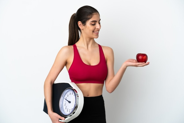 Młoda kaukaska kobieta na białym tle trzymająca wagę, patrząc na jabłko