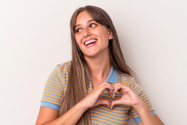 Młoda kaukaska kobieta na białym tle uśmiecha się i pokazuje kształt serca rękami.