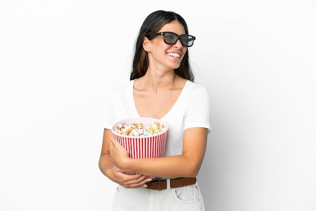 Młoda kaukaska kobieta na białym tle w okularach 3d i trzymająca duże wiadro popcornów