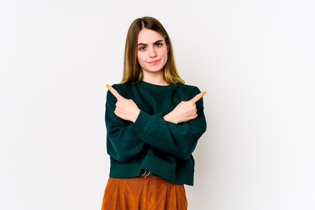 Młoda kaukaska kobieta na białym tle wskazuje na boki, próbuje wybrać jedną z dwóch opcji.