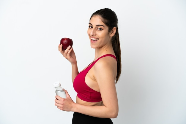 Młoda kaukaska kobieta na białym tle z jabłkiem i butelką wody