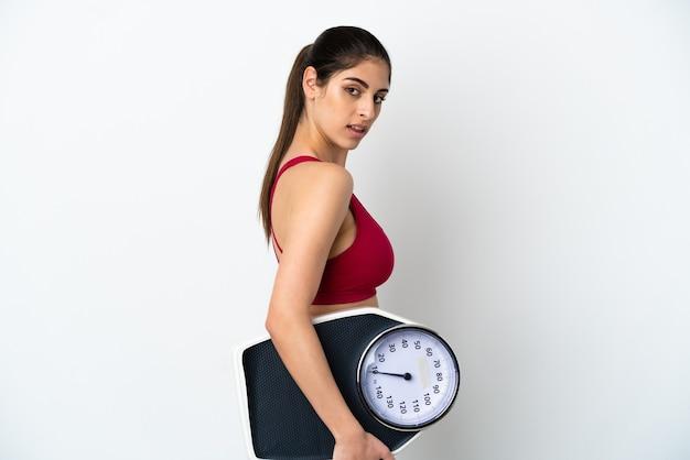 Młoda kaukaska kobieta na białym tle z maszyną do ważenia