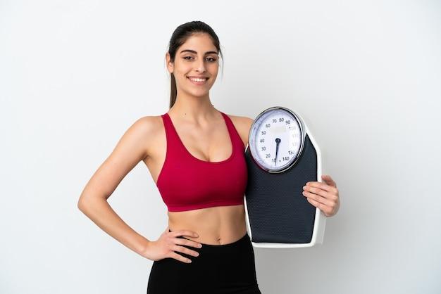 Młoda kaukaska kobieta na białym tle z wagą