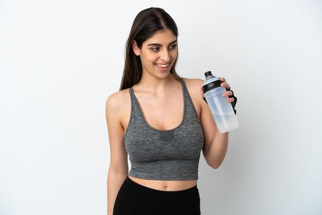 Młoda kaukaska kobieta na białym tle ze sportową butelką na wodę