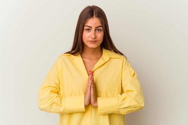 Młoda kaukaska kobieta na białym tle zszokowana, zakrywająca usta rękami, chcąca odkryć coś nowego.