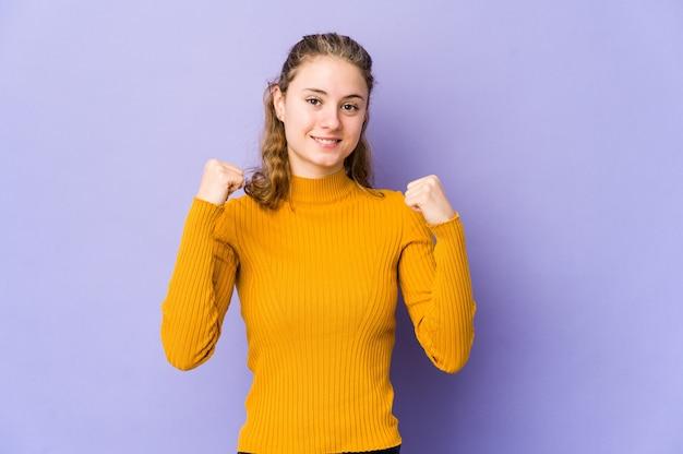 Młoda kaukaska kobieta na fioletowej ścianie świętuje zwycięstwo, pasję i entuzjazm, szczęśliwy wyraz.