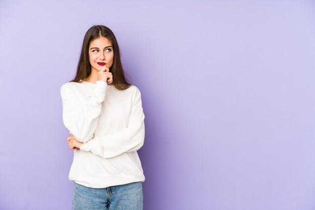 Młoda kaukaska kobieta na fioletowym spojrzeniu z boku z wyrazem wątpliwości i sceptycyzmu.