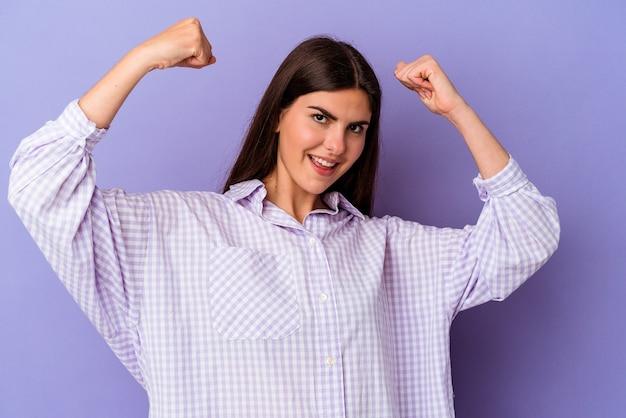 Młoda kaukaska kobieta na fioletowym tle pokazująca gest siły z ramionami, symbol kobiecej mocy