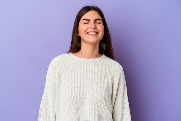 Młoda kaukaska kobieta na fioletowym tle śmieje się i zamyka oczy, czuje się zrelaksowana i szczęśliwa.