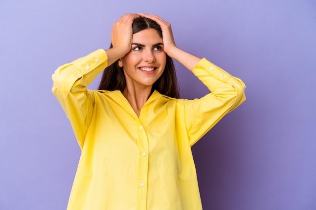 Młoda kaukaska kobieta na fioletowym tle śmieje się radośnie trzymając ręce na głowie. koncepcja szczęścia.