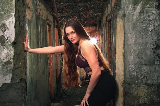 Młoda kaukaska kobieta na korytarzu zrujnowanego budynku w środku lasu.