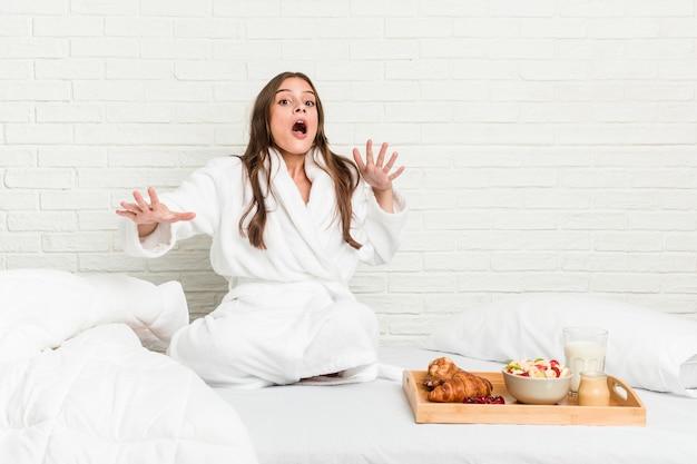 Młoda kaukaska kobieta na łóżku jest w szoku z powodu zbliżającego się niebezpieczeństwa