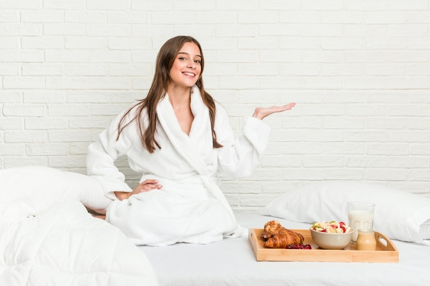 Młoda kaukaska kobieta na łóżku, pokazując miejsce na kopię na dłoni i trzymając drugą rękę na talii.