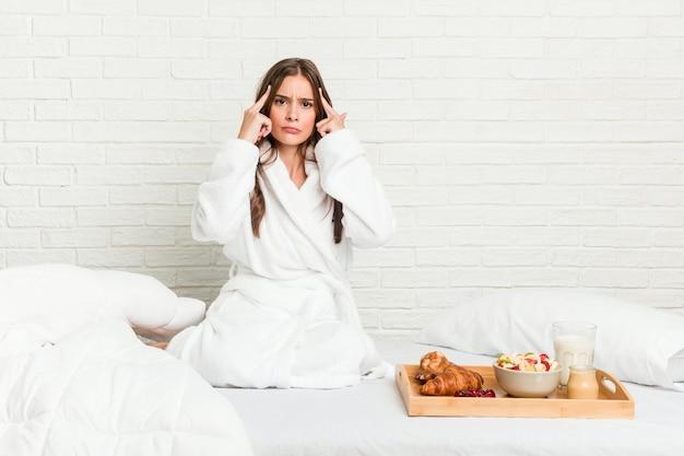 Młoda kaukaska kobieta na łóżku skupiła się na zadaniu, trzymając wskazujące głowę palce.