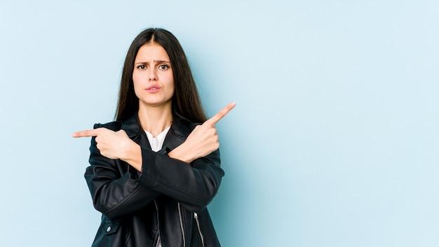 Młoda kaukaska kobieta na niebieskiej ścianie wskazuje na boki, próbuje wybrać jedną z dwóch opcji.
